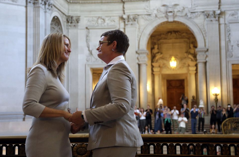 Sandy Stier, left, exchanges wedding vows with Kris Perry during a ceremony presided by California Attorney General Kamala Ha