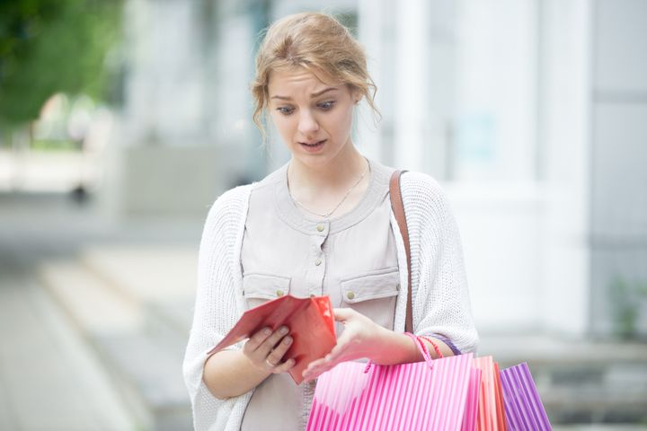 Portrait of unhappy stressed beautiful person looking in open wallet with shocked expression while holding color shopping bag