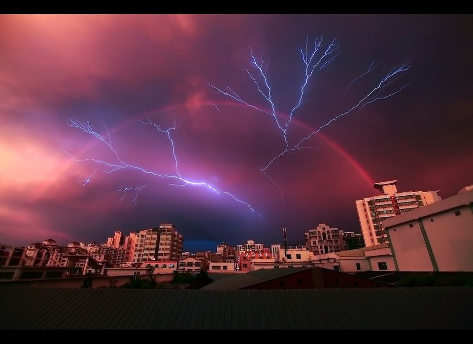 A rainbow appears in the sky as lightning strikes during a rainstorm on May 13, 2012 in Haikou, China. (Photo credit: China F