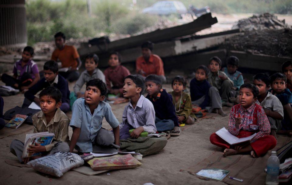 In this photo taken Tuesday, Nov. 6, 2012, underprivileged Indian children attend a free school run under a metro bridge in N