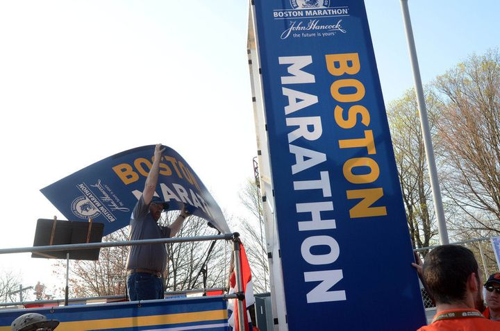 HOPKINTON, MA - APRIL 16: A volunteer hangs up the start banner at the start of the 116th running of the Boston Marathon Apri