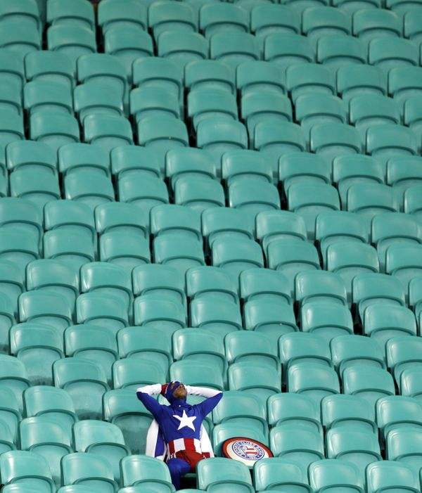 A lone U.S. supporter dressed as 'Captain America' sits in the stands after Belgium defeated the U.S. 2-1 in extra time to ad