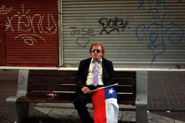 A man holding Chile's national flag sits alone on a street bench after Chile was defeated by Brazil at a World Cup round of 1