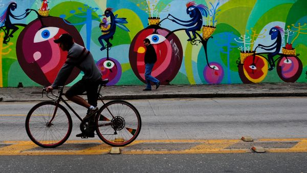 A man rides a bicycle as a man walks past a mural in Curitiba, Brazil, one of the host cities for the 2014 soccer World Cup,
