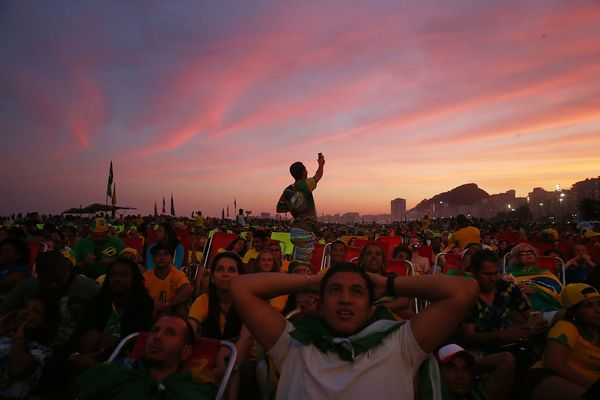 Brazil fans watch a live broadcast of the Brazil-Cameroon match at the FIFA Fan Fest on Copacabana Beach as a helicopter flie