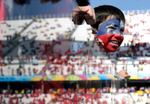 A young Chilean fan looks out onto the pitch before the group B World Cup soccer match between the Netherlands and Chile at t