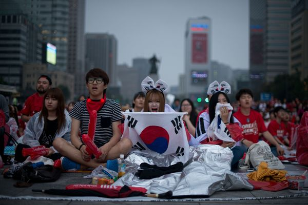 South Korean football fans react as their team loses to Algeria in the 2014 World Cup in Brazil, as they watch the match on g