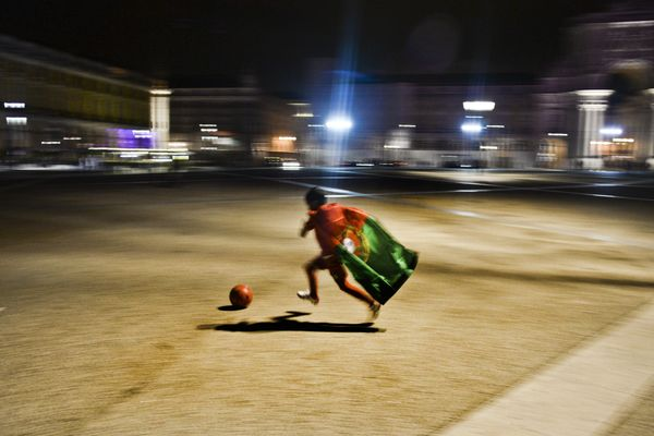 A child wearing the Portuguese national football team dribbles a ball at Terreiro do Paco Square in Lisbon on June 22, 2014 d