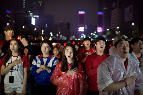 South Korean football fans sing their national anthem as they watch their team play against Algeria in the 2014 World Cup in