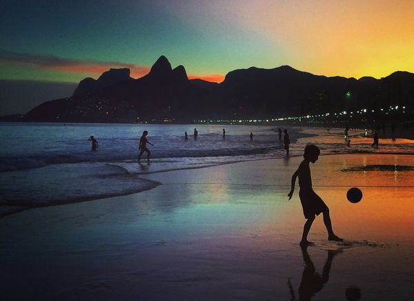 A young boy plays football at sunset on June 8, 2014 in Rio de Janeiro, Brazil. (Photo by Clive Rose/Getty Images)