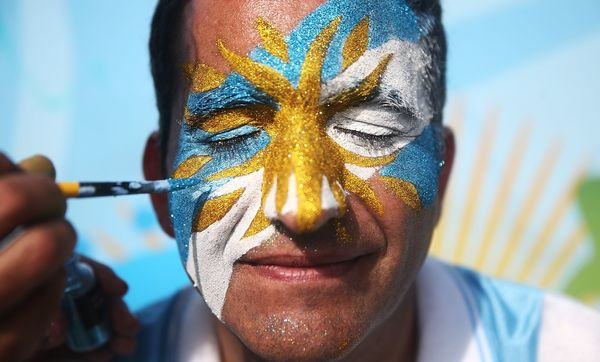 An Argentina fan has his face painted before the start of the Argentina match outside FIFA Fan Fest on June 21, 2014 in Rio d