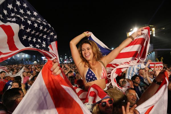 Fans of the U.S. national soccer team celebrate their team's victory during a live broadcast of the soccer World Cup match be