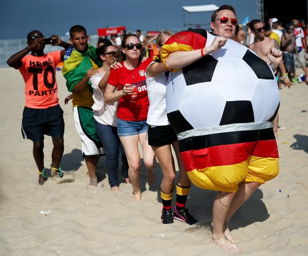 German and other soccer fans create a conga line while waiting for the start of the German vs. Portugal match as they watch o