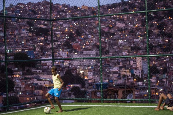 A boy plays with a football as the Netherlands and Spain play FIFA World Cup 2014 football match, at the Rocinha shantytown i
