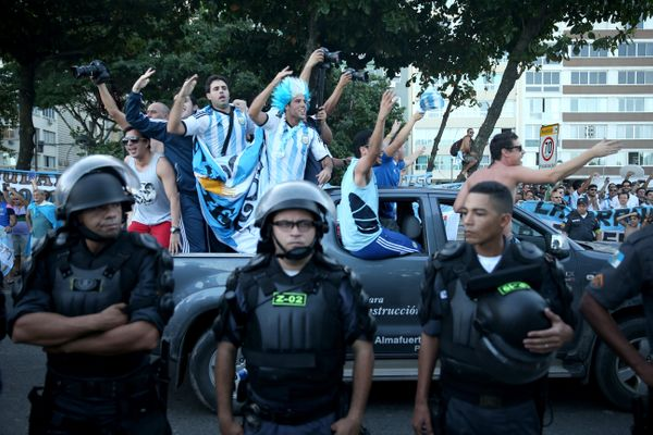 A pickup truck with Argentine football fans drive past riot police trying to control the fans and keep them from impeding veh