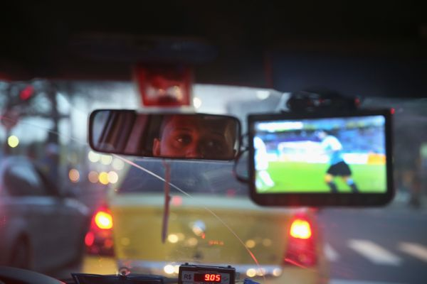 A taxi driver watches Uruguay and Costa Rica play on his small television set as the FIFA World Cup continues on June 14, 201