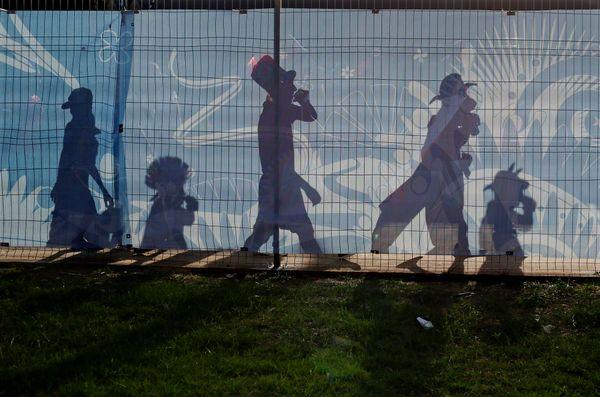 The shadows of Chile soccer fans are cast on a fence outside the Arena Pantanal as they arrive to their team's World Cup matc