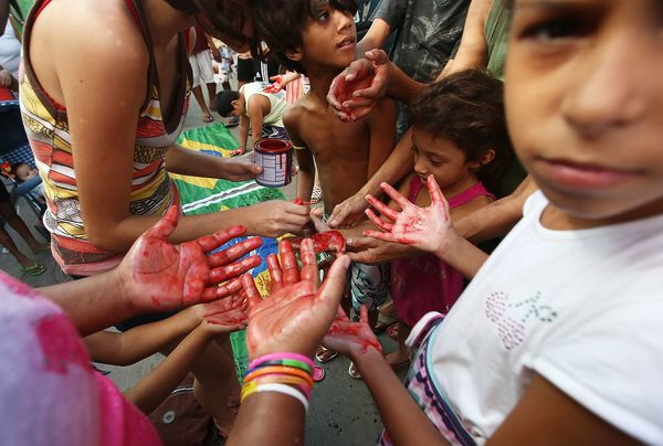 Young residents gather red paint on their hands, symoblizing the blood of Mare residents killed, where protestors painted a s