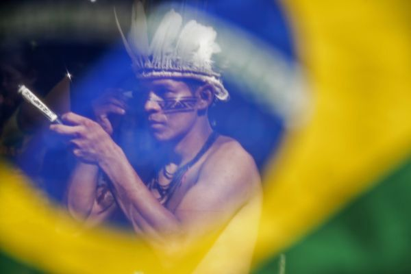 A Brazilian Satere-Mawe indigenous man waits to watch the FIFA World Cup inaugural match between Brazil and Croatia, on June