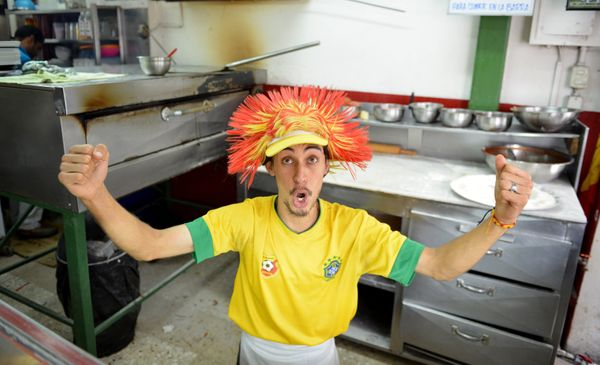 A worker at a pizza store celebrates in San Jose after Costa Rica defeated Uruguay in the FIFA World Cup Brazil Group D match