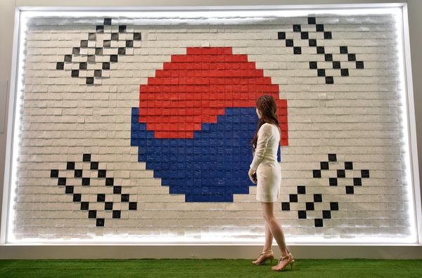A woman looks at the South Korean flag made with messages supporting South Korea's national football team at the Korea House