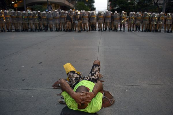 A protester lies on the ground before a line of riot police during a demonstration against the FIFA World Cup in Belo Horizon
