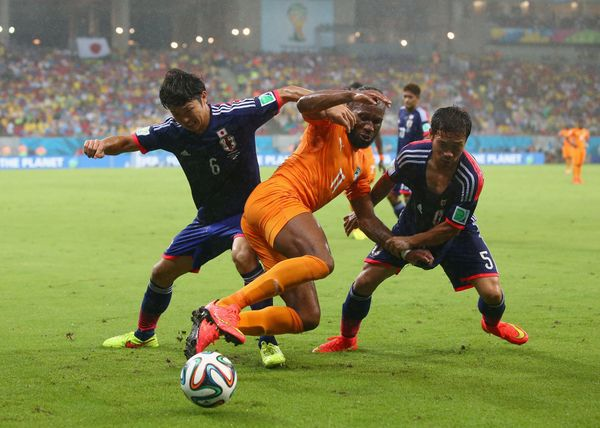 Masato Morishige (L) and Yuto Nagatomo of Japan challenge Didier Drogba of the Ivory Coast during the 2014 FIFA World Cup Bra