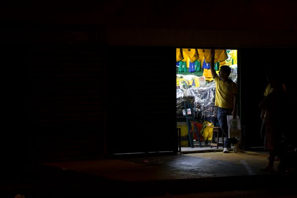 A man closes a shop selling clothing, including the Brazilian national football team strip, in downtown Manaus on June 13, 20