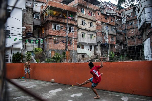 Boys play with a football as the Netherlands and Spain play FIFA World Cup 2014 football match, at the Rocinha shantytown in