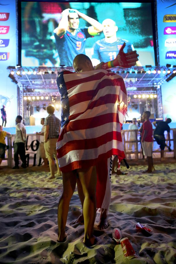 A couple embraces with the American flag wrapped around them as they watch the football game featuring Spain vs. Netherland o