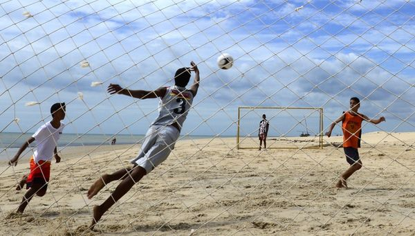 Brazilian kids play football on the beach of Cumbuco, Ceara, on June 13, 2014 during the 2014 FIFA World Cup.     AFP PHOTO /