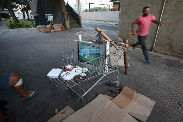 A man runs after exiting the subway to watch the Brazil-Croatia match from a television jerry-rigged on a shopping cart on Ju