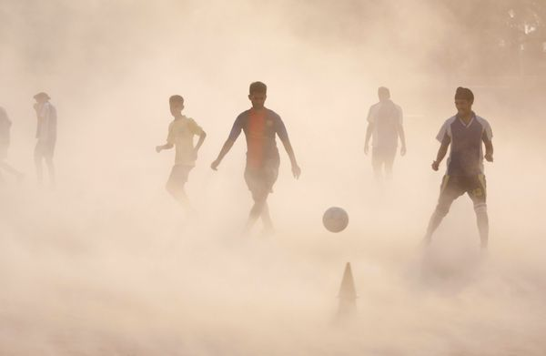 Aspiring young Indian soccer players continue with their practice during a dust storm in Jammu, India, Wednesday, June 11, 20