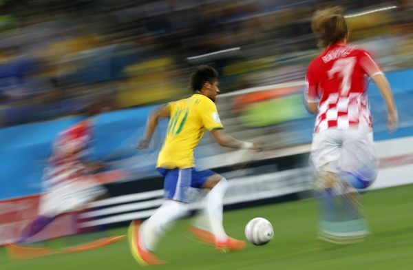 Brazil's forward Neymar (C) runs with the ball during a Group A football match between Brazil and Croatia at the Corinthians