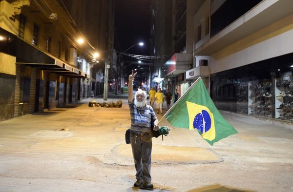 A supporter of the Brazilian national football team holds a flag as he celebrates his team's win against Croatia, in Ribeirao
