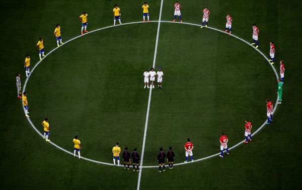 Brazil and Croatia players stand around the center circle as doves are released before the 2014 FIFA World Cup Brazil Group A
