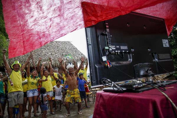 Brazilian Satere-Mawe indigenous peopel celebrates as they gather to watch the FIFA World Cup inaugural match between Brazil