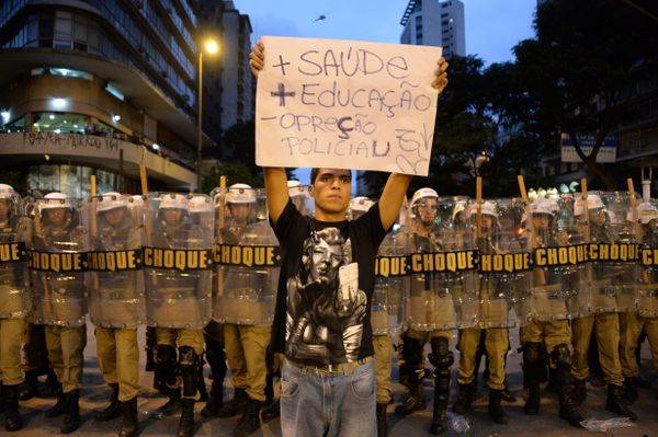 A protester raises a placard in front of a line of riot police during a demonstration against the 2014 FIFA World Cup in Belo