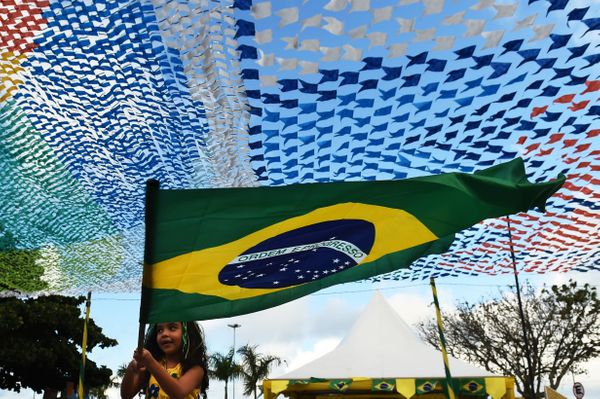 A young supporter of the Brazilian national football team waves a flag on June 12, 2014 in Porto Seguro before the opening ma