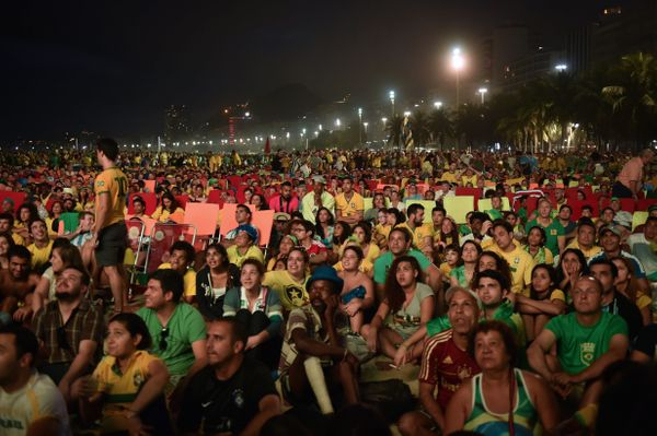 People watch on a huge screen the Brazil vs Croatia opening match during the FIFA Fan Fest in Copacabana Beach in Rio de Jane