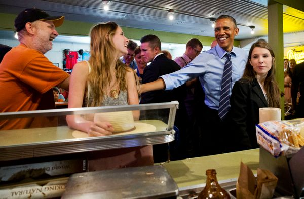 President Barack Obama jokes with patrons as he orders barbecue for himself and the people in the front of the line at Frankl
