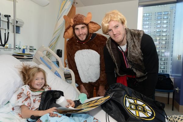 Boston Bruins Matt Bartkowski and Kevan Miller spend time with Sarah at Boston Children's Hospital on October 27, 2014 in Bos