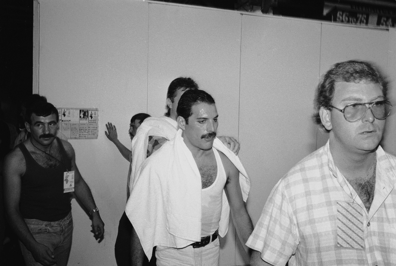 1985년 7월 13일, 잉글랜드 웸블리 스타디움에서 열린 'Live Aid' 콘서트를 앞둔 프레디 머큐리를 대기실에서 찍은 모습. 왼쪽 뒤에 검은 옷을 입고 머큐리를 따라가는 남성이 짐 허튼이다.