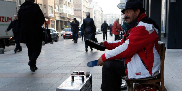 In this Friday, Dec. 19, 2014, photo shoe shiner Ramiz Hasani waits for customers on the main street in Sarajevo, Bosnia.  Ra