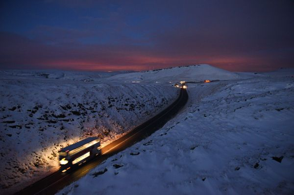 A double-decker bus travels over Standedge between snow-covered fields at dusk near the village of Diggle, northern England.