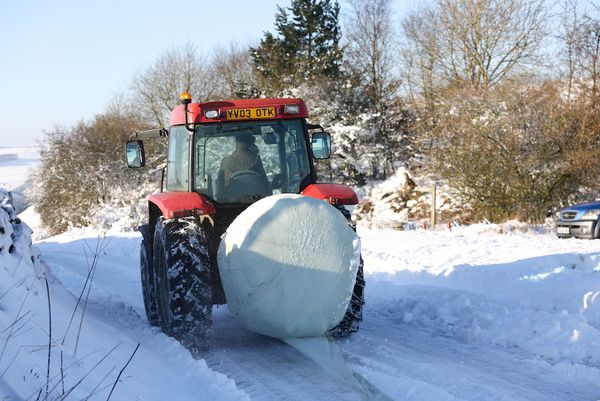 Tractor drives along the road on Curbar Gap during snowy weather in Derbyshire, Britain