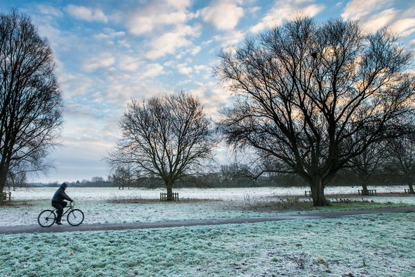 A cyclist out in freezing conditions at sunrise in Cambridge after the coldest night of the year