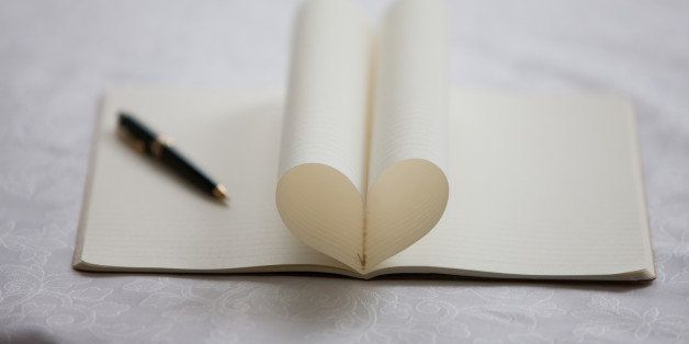 Pen and pages of notebook forming heart-shape