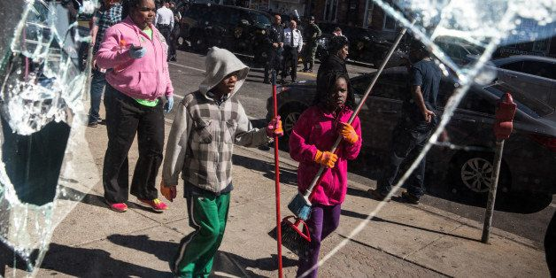 BALTIMORE, MD - APRIL 28:  People helping to clean up debris caused by rioting yesterday after the funeral of Freddie Gray ar