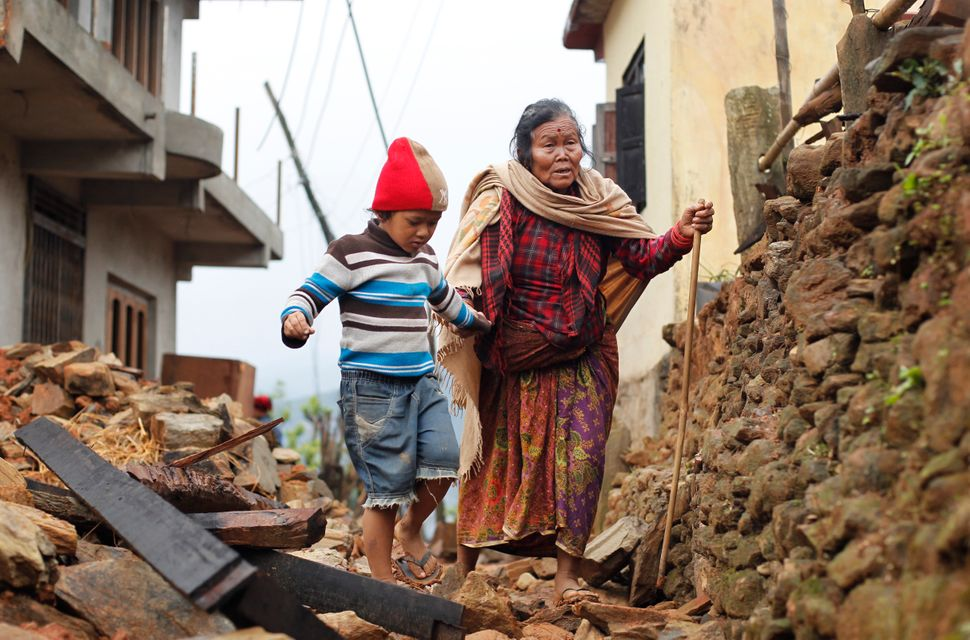 Jagot Kumari Rana, 79, is led through the rubble of collapsed homes by her grandson Sogat Rana, 7, in Paslang village near th